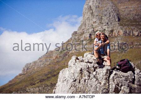Coppia escursionisti seduta su roccia in montagna uomo abbracciando la donna guardando paesaggi vista anteriore Foto Stock