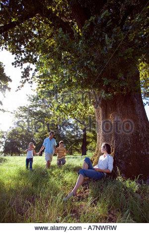 Padre camminando mano nella mano con due bambini 7 10 nella radura boschiva madre in appoggio contro la struttura Foto Stock