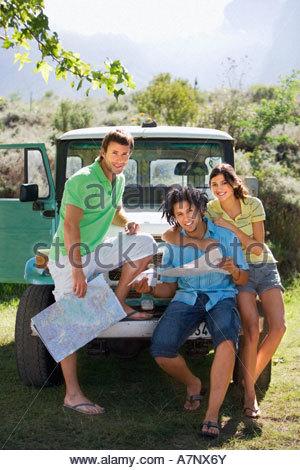 Giovane donna e due amici maschi appoggiata contro la jeep parcheggiata consulting road map ritratto sorridente Foto Stock