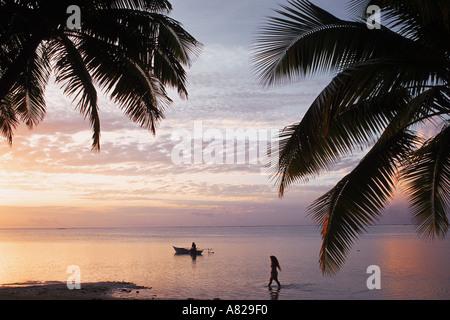 Una donna a piedi e una canoa outrigger canoa sull'isola di Aitutaki nelle Isole Cook