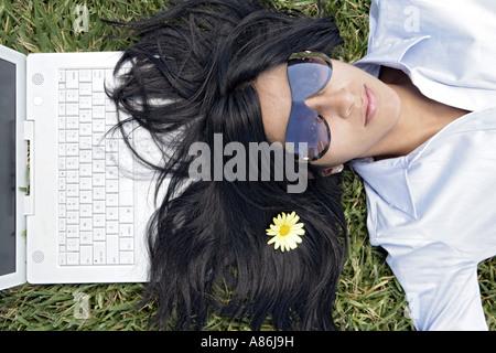 Vista di una donna che dorme sul prato con un fiore tra i capelli. Foto Stock