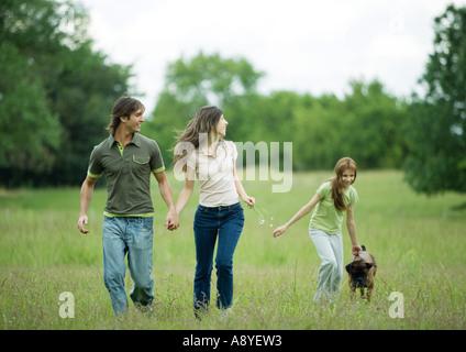 Giovane adulto giovane camminando con la ragazza e cane Foto Stock