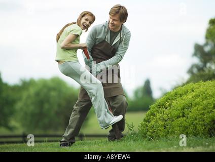 Ragazza in piedi sulla pala, ridere mentre il giovane uomo detiene la pala Foto Stock