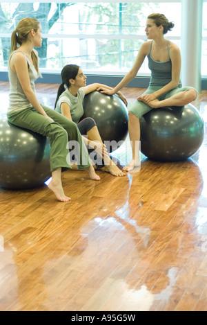 Giovani donne seduti sulle sfere di fitness, chat Foto Stock
