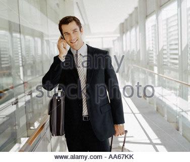 Maschio di business traveler parlando al cellulare Foto Stock