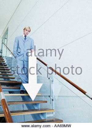 Imprenditore su scale vuoto con la freccia rivolta verso il basso Foto Stock