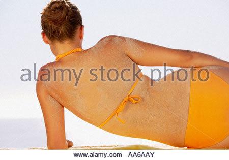 Vista posteriore della donna in bikini con sabbia sul retro Foto Stock