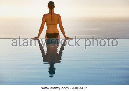 Donna seduta sul bordo della piscina a sfioro in bikini Foto Stock