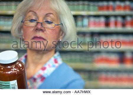 Donna esaminando il vaso in negozio Foto Stock