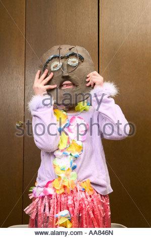 Giovane ragazza con maschera di legno sopra il suo volto Foto Stock