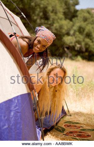 Due giovani donne prendendo le loro teste fuori da una tenda Foto Stock
