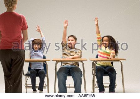 Gli studenti con le mani alzate nella classe Foto Stock