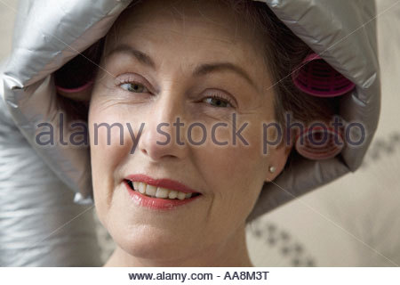 Senior donna seduta sotto asciugacapelli Foto Stock