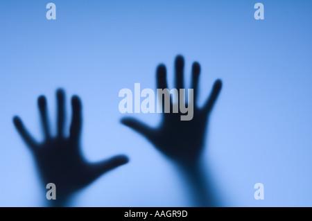 Vista astratta di due mani dietro un vetro smerigliato Foto Stock