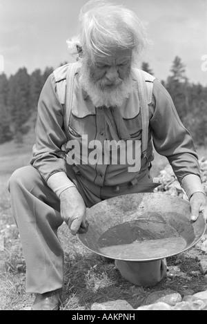 Negli anni quaranta anni cinquanta anziani uomo barbuto PROSPECTOR PANNING PER ORO Foto Stock