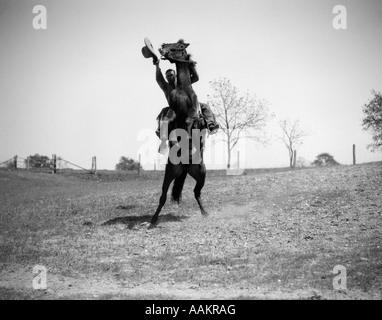 1920s 1930 cowboy sull allevamento di cavalli up uomo sventolando il cappello in mano Foto Stock