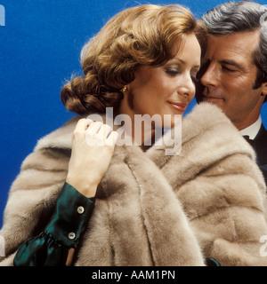 Anni Settanta l uomo e la donna che indossa la pelliccia nell intimo abbraccio Foto Stock