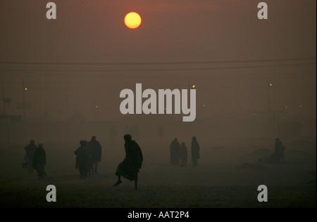 KUMBH MELA INDIA 2001 come il sole tramonta il fumo di fuochi di legno crea una spessa smog pellegrini tornare nei Foto Stock