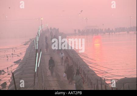 KUMBH MELA INDIA 2001 come il sole tramonta pellegrini fanno la loro strada attraverso i ponti temporanei nei loro Foto Stock