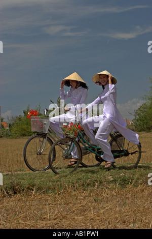 Due giovani donne in cappelli conici e tradizionale di colore bianco ao dai costume in bici sul percorso di campi Foto Stock