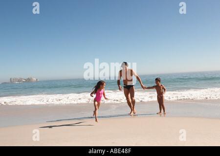 Padre e figli in esecuzione su una spiaggia Foto Stock