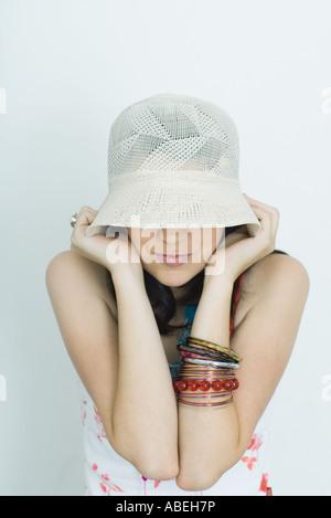 Ragazza adolescente tirando hat giù sopra gli occhi, ritratto Foto Stock