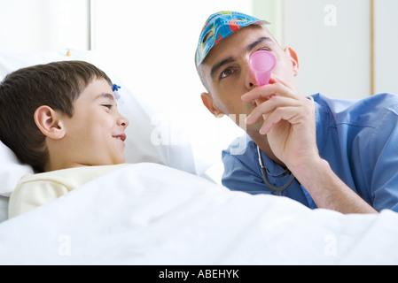 Intern accanto al ragazzo nel letto di ospedale, indossando maschera e partito di soffiaggio avvisatore acustico