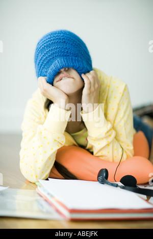 Giovane donna sdraiata sul pavimento, tirando knit hat giù sopra gli occhi Foto Stock