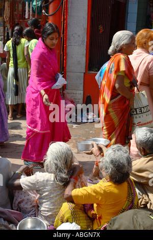 Donna dà il riso ai poveri beggers sul Ghats del fiume Gange, Varanasi, India Foto Stock