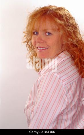 Ricci con testa rossa donna guardando sopra la spalla Foto Stock