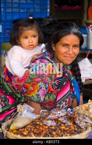 Locale donna colorati con grand figlia sul retro nel mercato del villaggio turistico di Antigua Guatemala Foto Stock