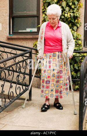 Donna anziana con due bastoni da passeggio a piedi verso il basso una rampa lasciando un assistenza residenziale home concentrando per evitare cadute