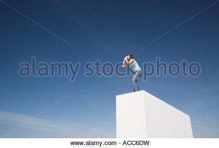 Donna in piedi sul muro esterno gridando Foto Stock