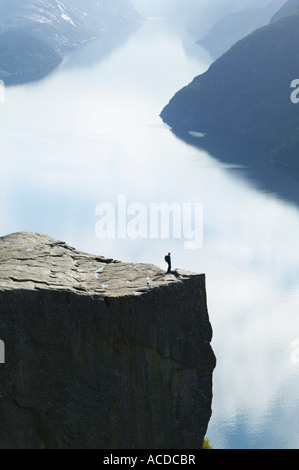 Walker in piedi sul Prekestolen, pulpito o roccia, sopra Lysefjorden, Forsand, Rogaland, Norvegia. Foto Stock