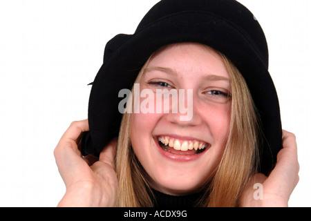 Foto di un elegante sorridente ragazza adolescente tirando il suo cappello nero verso il basso sopra le sue orecchie Foto Stock