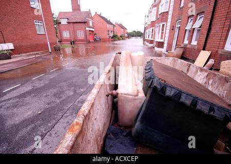 Allagata strada residenziale di Upton su Severn WORCESTERSHIRE REGNO UNITO dopo il mese di luglio le inondazioni del 2007 con skip piena di mobili danneggiati Foto Stock