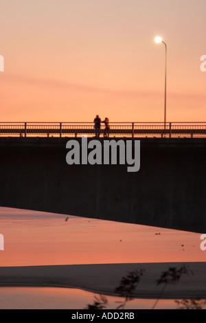 Due persone in piedi sul lao ponte giapponese attraverso il fiume Mekong al tramonto Foto Stock