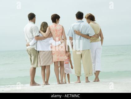 Gruppo in piedi vicino al bordo dell'acqua sulla spiaggia, vista posteriore Foto Stock