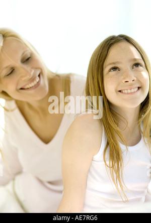 Ragazza sorridente e guardando in alto, madre guardandosi le spalle Foto Stock