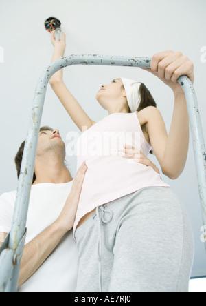 Uomo con l uomo sulla scala come essa cambia lampadina