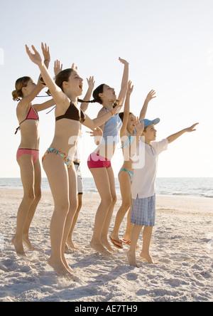 Un gruppo di ragazzi del salto e sventolare sulla spiaggia Foto Stock