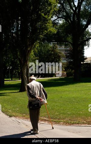 Il vecchio uomo a camminare in un parco su un luminoso giorno di estate Foto Stock