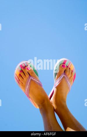 Verticale fino in prossimità dei piedi conciate con dipinto toenails indossando striped flip flop contro un luminoso Foto Stock