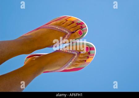 Orizzontale fino in prossimità dei piedi conciate con dipinto toenails indossando striped flip flop contro un luminoso Foto Stock