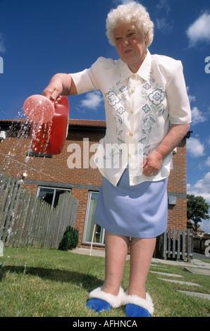 Una signora anziana indossando pantofole acque il suo giardino con un annaffiatoio durante la penuria d acqua Foto Stock