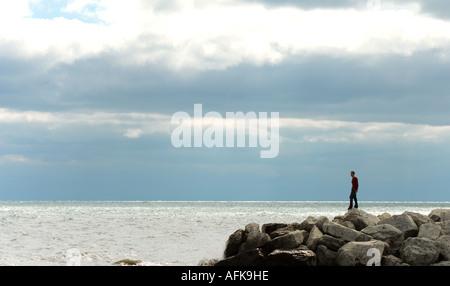 Silhouette di un giovane uomo in piedi sulle rocce sul lungolago di Milwaukee, Wisconsin USA Foto Stock