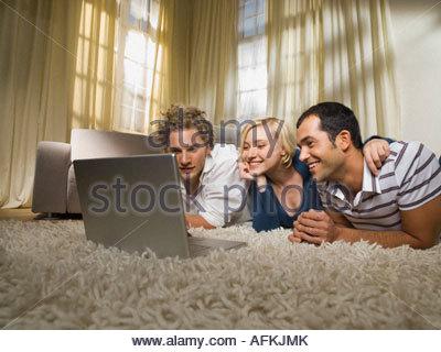 Gli amici a guardare qualcosa sul laptop. Foto Stock