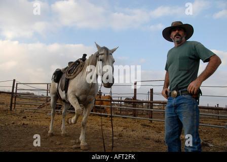 Un allevatore israeliano di bestiame che indossa una pistola in un cortile nelle alture del Golan nord Israele