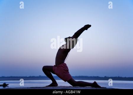 Famosa in tutto il mondo yogi insegnante Dr Rakesh Yogi in virbhadrasana yoga postura Fiume Gange India Foto Stock