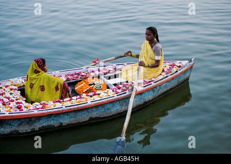 Due donna in una barca sul fiume Gange vendere deepak o lampade a olio del Fiume Gange Varanasi india Foto Stock